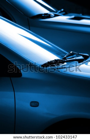 Black and blue image with the detail of the windshield wipers of two cars - stock photo