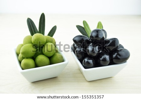 Black and Green Olives with leaves on a white background - stock photo