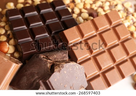 Black and milk chocolate bars with hazelnuts close up - stock photo