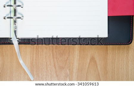 Black and red leather cover of binder notebook on wood floor. - stock photo