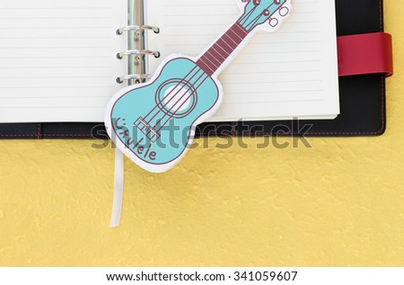 Black and red leather cover of binder notebook with lovey guitar on wood floor. - stock photo