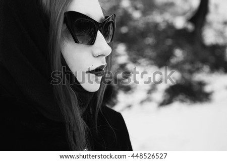 black and white art photography monochrome, stylish girl with pale skin, dark lips with a shawl on her head in black coat on background of a winter forest, woman with black sunglasses portrait profile - stock photo