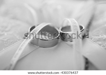 black and white art weeding photography monochrome, infinity sign of the rings, wedding rings on a white background,wedding bands, wedding rings on a cushion - stock photo