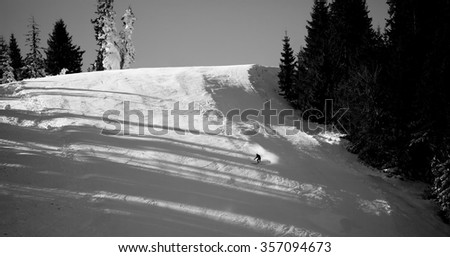 Black and white background of skier riding on slope- bulgarian winter resort of Pamporovo  - stock photo