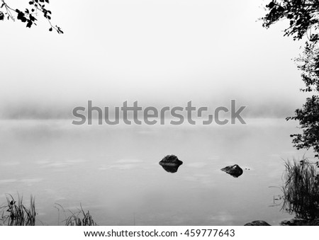 Black and white background. Reflection of stones in tranquil Alps lake at autumn   - stock photo