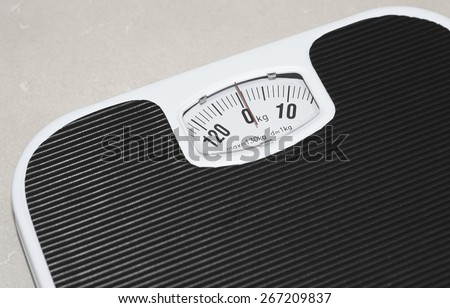 Black and white bathroom scales on tiled floor - stock photo