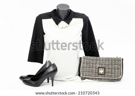 Black and white blouse on mannequin with matching accessories. Elegant blouse on tailor's dummy with matching purse,high heels and necklace - stock photo