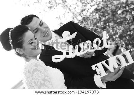 Black and white bride and groom having fun and posing with Sweet Love letters in sunlight  - stock photo