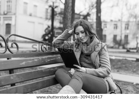 Black and White. BW. Young woman sitting with Tablet and reading from ebook - stock photo