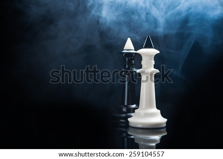 Black and white chess kings on dark background - stock photo