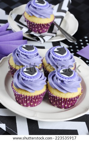 Black and white chevron with purple theme party luncheon table place setting for Melbourne Cup, Australian public holiday, horse race event with cupcakes closeup. - stock photo