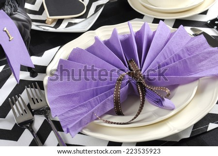 Black and white chevron with purple theme party luncheon table place setting for Melbourne Cup, Australian public holiday, horse race event - closeup. - stock photo