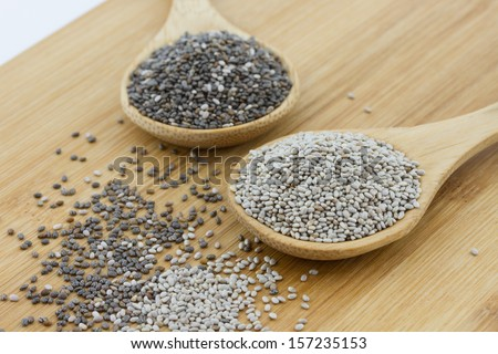 black and white chia seeds on wooden underground - stock photo
