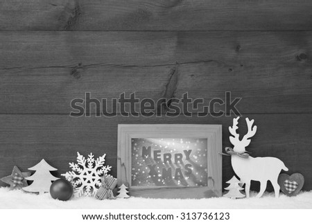 Black And White Christmas Decoration With Reindeer Christmas Trees Snowflake Ball On Snow. Picture Frame With English Text Merry Xmas. Christmas Card For Seasons Greetings. Wooden Background - stock photo