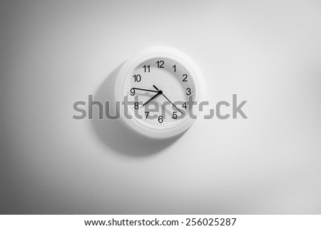 black and white clock hanging at the wall with copy space - stock photo