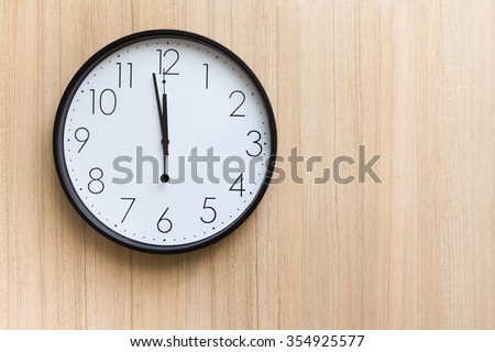 black and white clock shown almost mid day or mid night time on light wooden wall ,free space for text  concept : countdown for new year   - stock photo