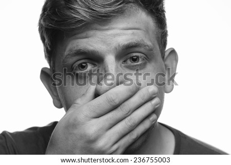 Black and white close-up image of young male with distance expression holding right hand across face looking away from camera.  - stock photo