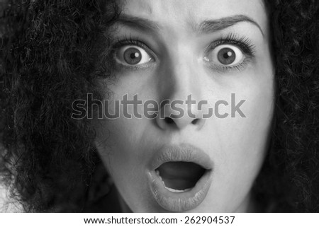Black and white close up of a frightened astonished woman with wide opened eyes and dramatic look. - stock photo