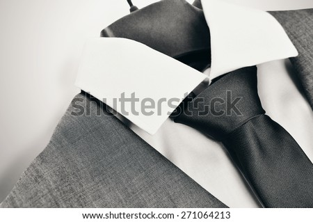 Black and white close-up of an elegant mans suit, collar and tie on clothes hanger on light grey background. - stock photo