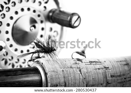Black and White Close up of fly fishing lure, rod and reel on white background - stock photo