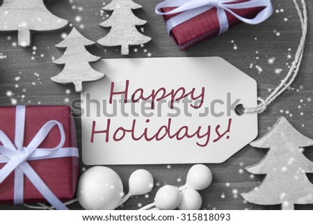Black and White Close Up Of Label With Ribbon,Red Gift,Present, Ribbon And Tree With Snowflakes. Christmas Decoration Or Card On Wooden Background. English Text Happy Holidays - stock photo