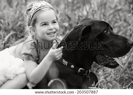 Black and white close up portrait of a beautiful young girl wearing a fancy dress, sitting on her dog pet back, smiling and enjoying a summer holiday. Active family with pets outdoors lifestyle. - stock photo