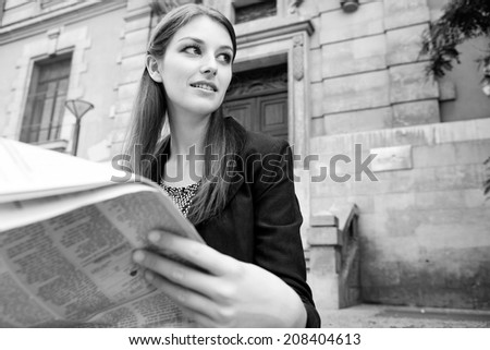 Black and white close up portrait of an attractive professional woman sitting by a classic stone building in the city reading a financial newspaper, thoughtful outdoors. Business communications news. - stock photo