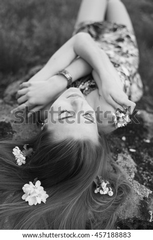Black and white close up portrait of beautiful blonde woman young cute girl laying on stone with flowers in her hair closing eyes dreaming outdoors image - stock photo