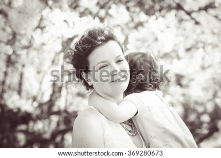 Black and white close up portrait of caucasian mother holding hugging cuddling  her daughter smiling on sunny spring summer day in park outside, Mothers day, retro vintage style, copyspace for text  - stock photo