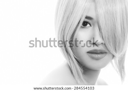 Black and white close-up portrait of young beautiful asian girl with stylish haircut over white background - stock photo