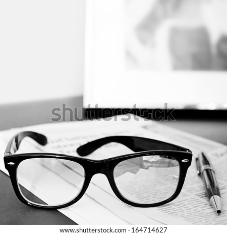 Black and white close up still life of a pair of reading glasses and a pen on an orange financial newspaper on a dark wooden writing desk with a family photo frame. Office interior with no people. - stock photo