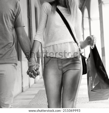Black and white close up view of a young tourist couple shopping and walking together holding hands while visiting a destination city on holiday in a classic city shopping mall store, relaxing. - stock photo