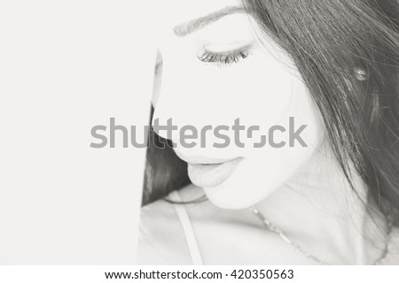 Black and white closeup portrait of beautiful young lady eyes closed at the window.  - stock photo
