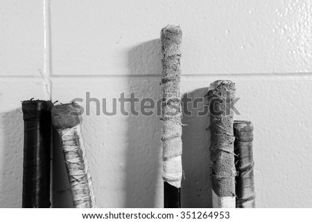 Black and white closeup shot of hockey sticks - stock photo