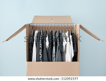 Black and white clothes hanging in a wardrobe box, prepared for moving. - stock photo