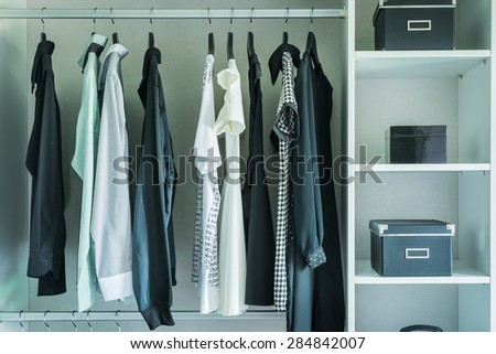 black and white clothes hanging in wardrobe - vintage style effect picture - stock photo