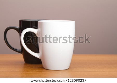 Black and white coffee mugs on wooden table - stock photo
