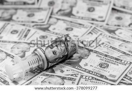 Black and white color of american dollars with syringe costs for the medical insurance,Focus on eye of 100 dollar roll and blurry background - stock photo