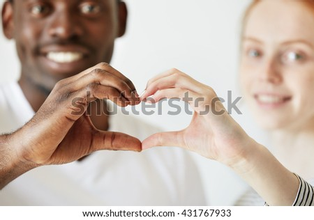 Black and white. Cropped portrait of African man and Caucasian woman looking and smiling at the camera, holding their hands in the shape of heart. Happy interracial couple. Selective focus on hands - stock photo