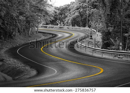 Black and white curve way of asphalt road in nature with yellow line. - stock photo