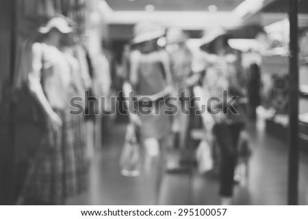 Black and white, de focused/Blur image of boutique window with dressed mannequins. Boutique display window with mannequins in fashionable dresses. - stock photo