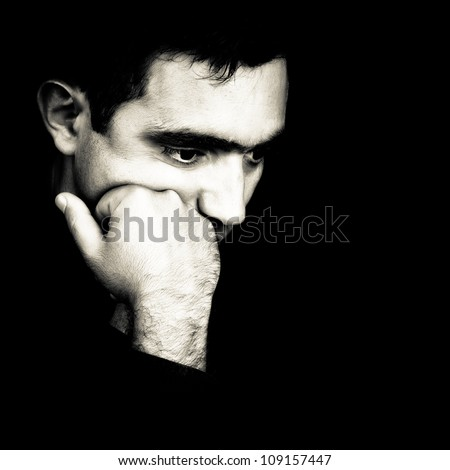 Black and white  dramatic close-up  of a man thinking with a fist on his chin emerging from a black background - stock photo