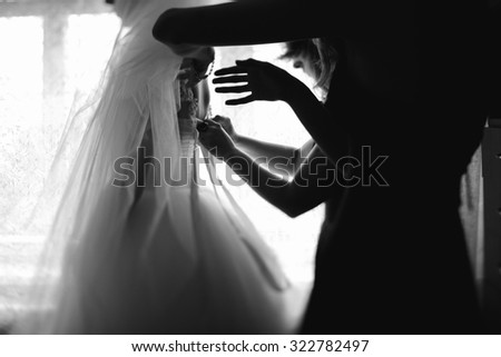 Black and white elegant luxury bride dressing up in stylish dress. preparation for wedding with bridesmaids - stock photo