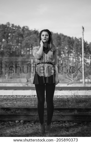 Black and white fashion shoot of gorgeous girl posing straight in full lenght outdoor wearing a leather skirt and a shirt with stripes - stock photo