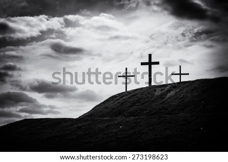 black and white filtered image of a silhouette of three crosses standing on hill with the sky lit up in the background a bright white light - stock photo
