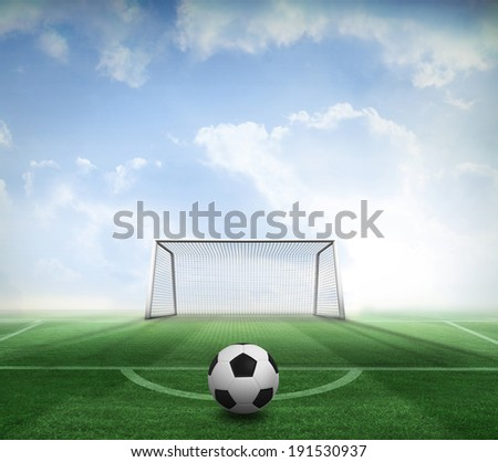 Black and white football against football pitch and goal under blue sky - stock photo