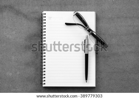 Black and white glasses and pen on notebook - stock photo