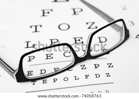 Black and white glasses on a eye sight test chart. Isolated on white background. - stock photo