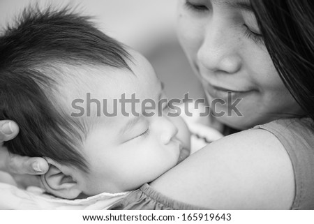 Black and White Happy asian mother with adorable cute baby - stock photo