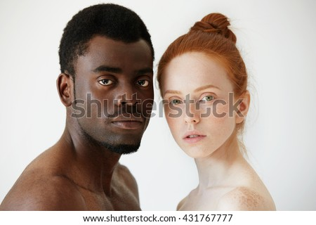 Black and white. Headshot of African man and Caucasian woman standing shirtless and looking at the camera with serious expression. Portrait of young beautiful interracial couple. Mixed race relations - stock photo